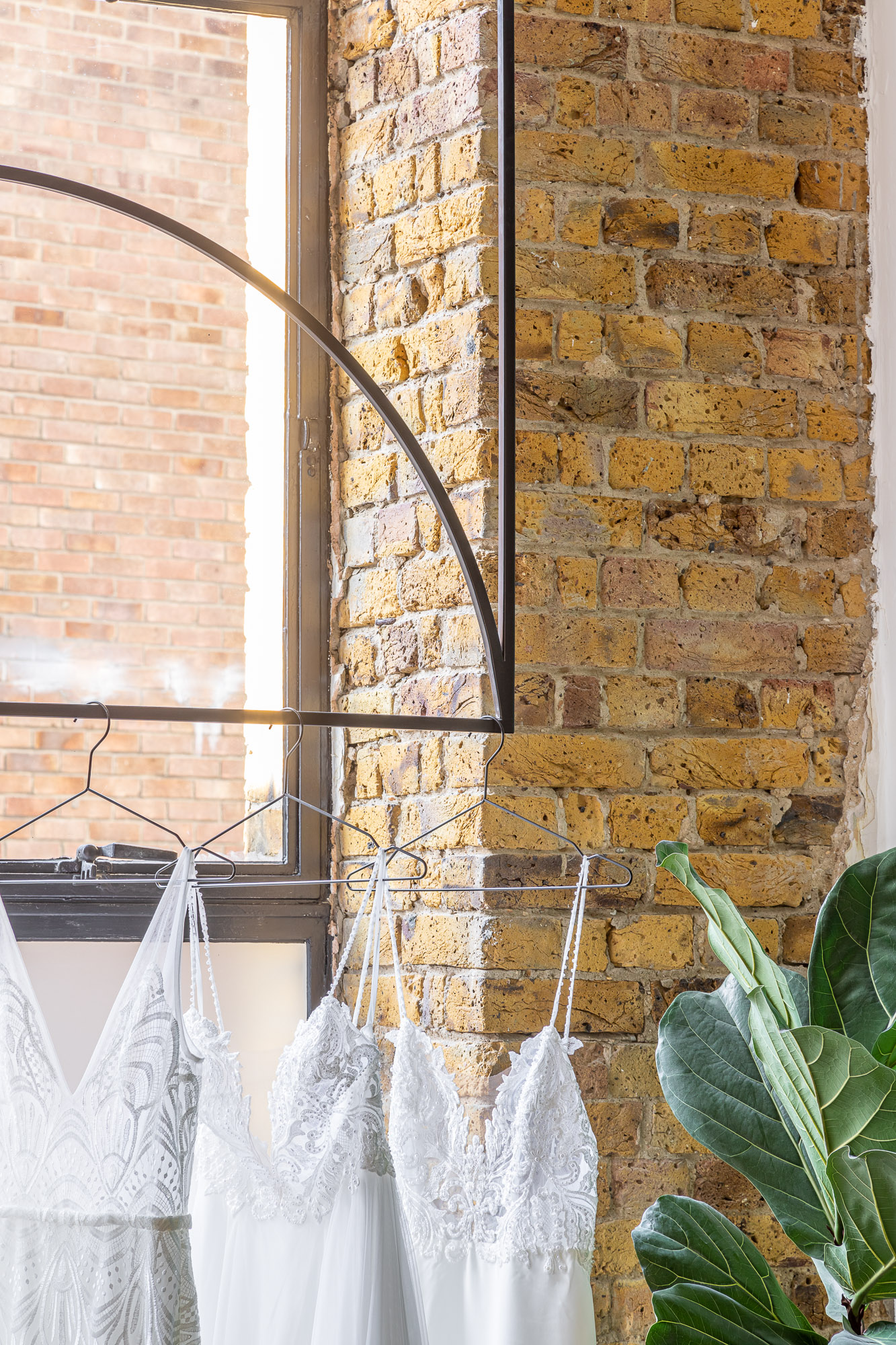 jonathan bond, interior photographer, brick wall corner hanging bridal dresses, made with love, london